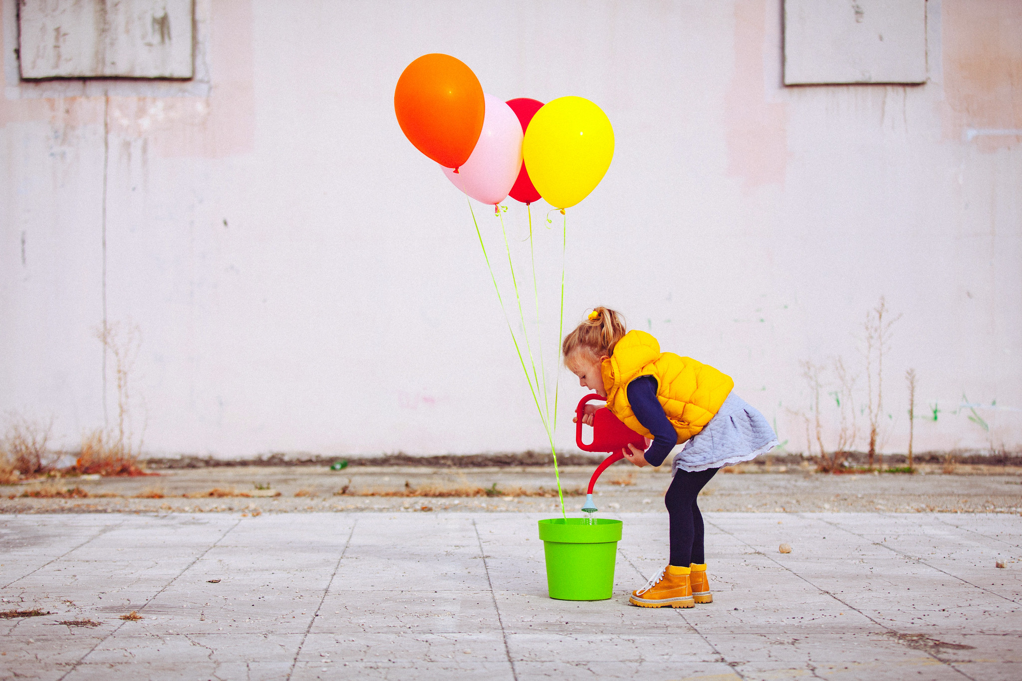 girl in yellow coat with watering can and balloons