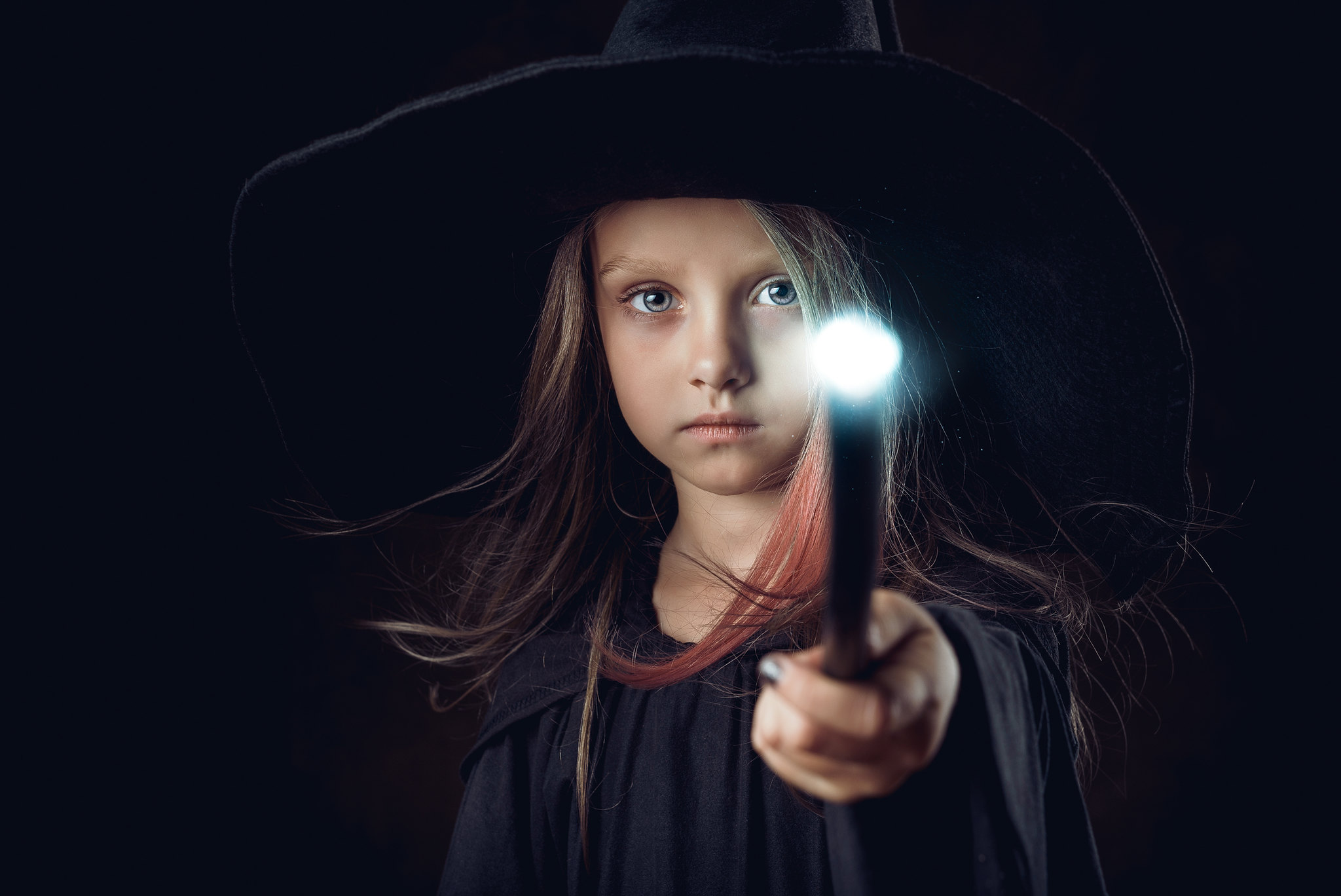 girl dressed as a witch holding a wand