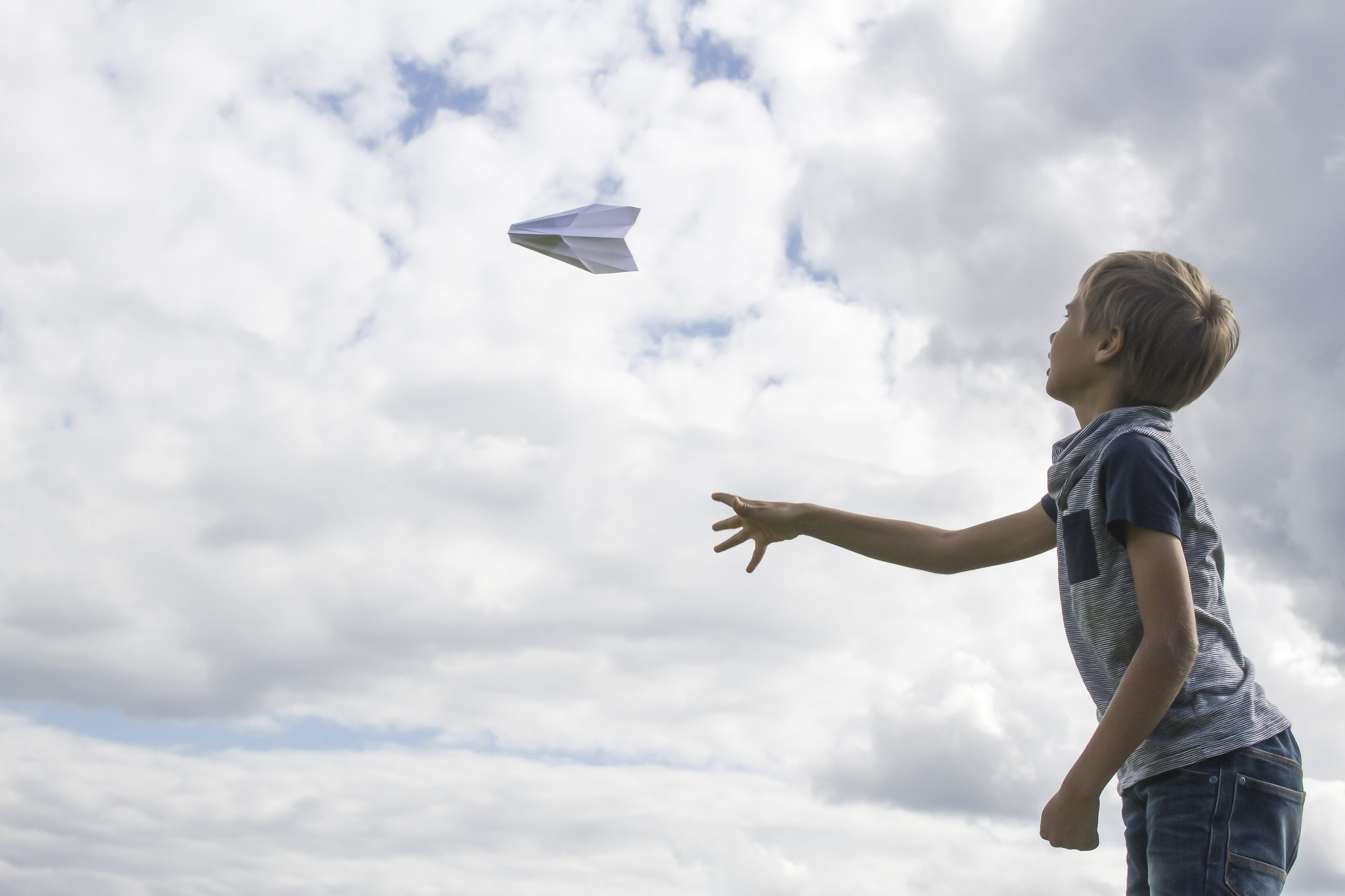 boy throwing paper airplane outside