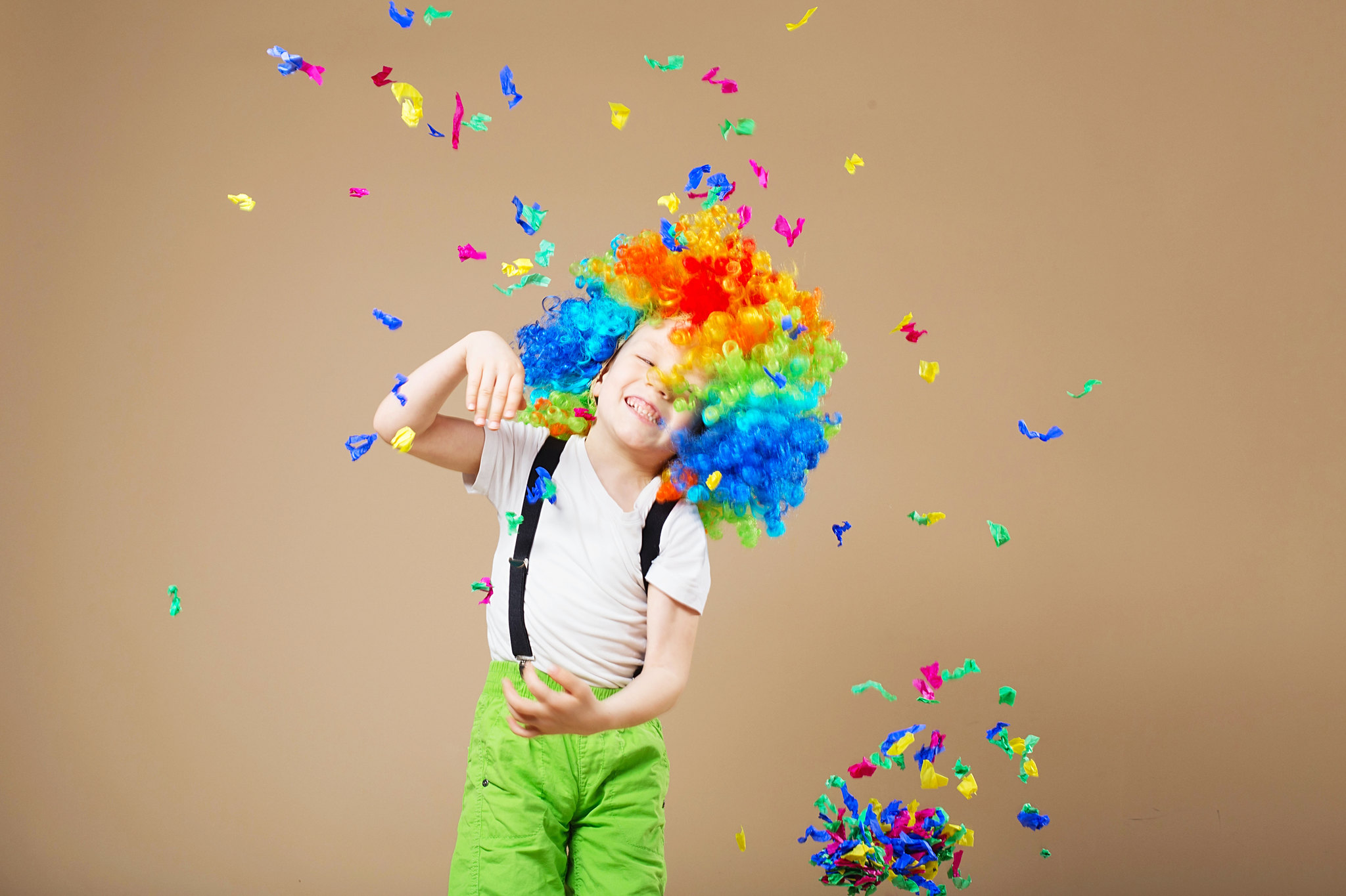 child dressed as a clown showered in confetti