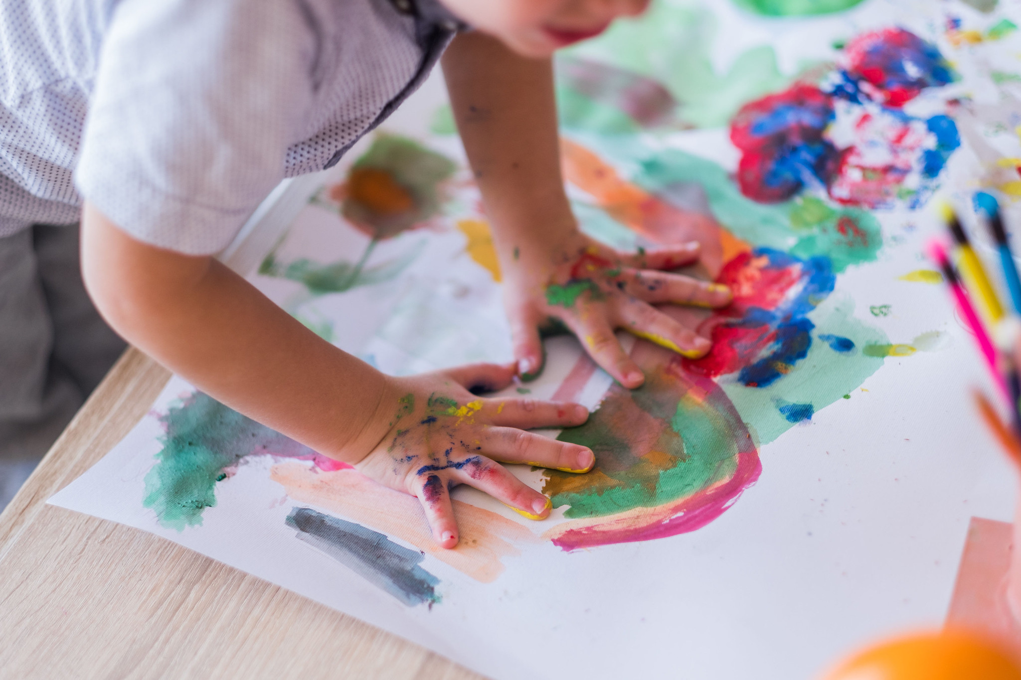 child using hands to paint and get messy