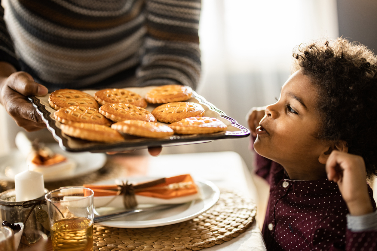 child with tray of mini pies
