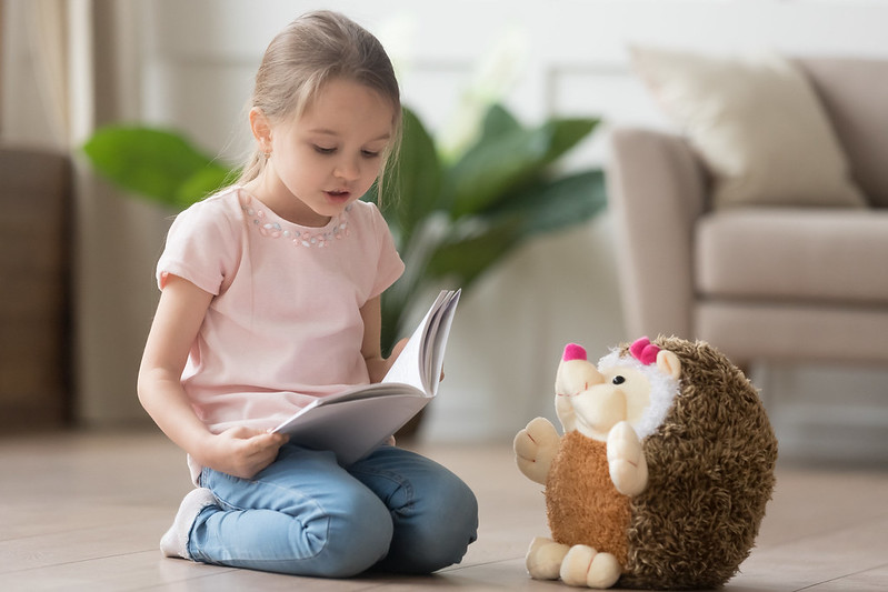 Child reading story to hedgehog toy