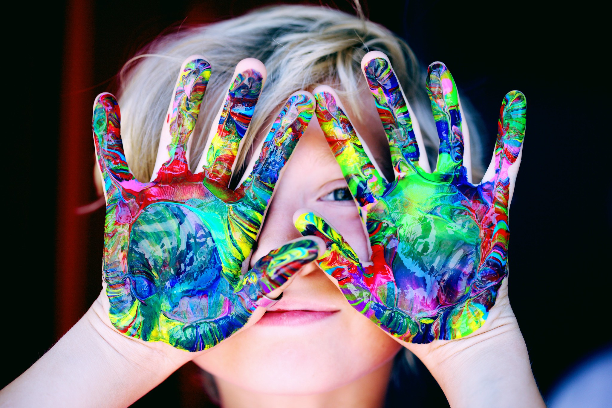 child holding up hands covered in neon paint