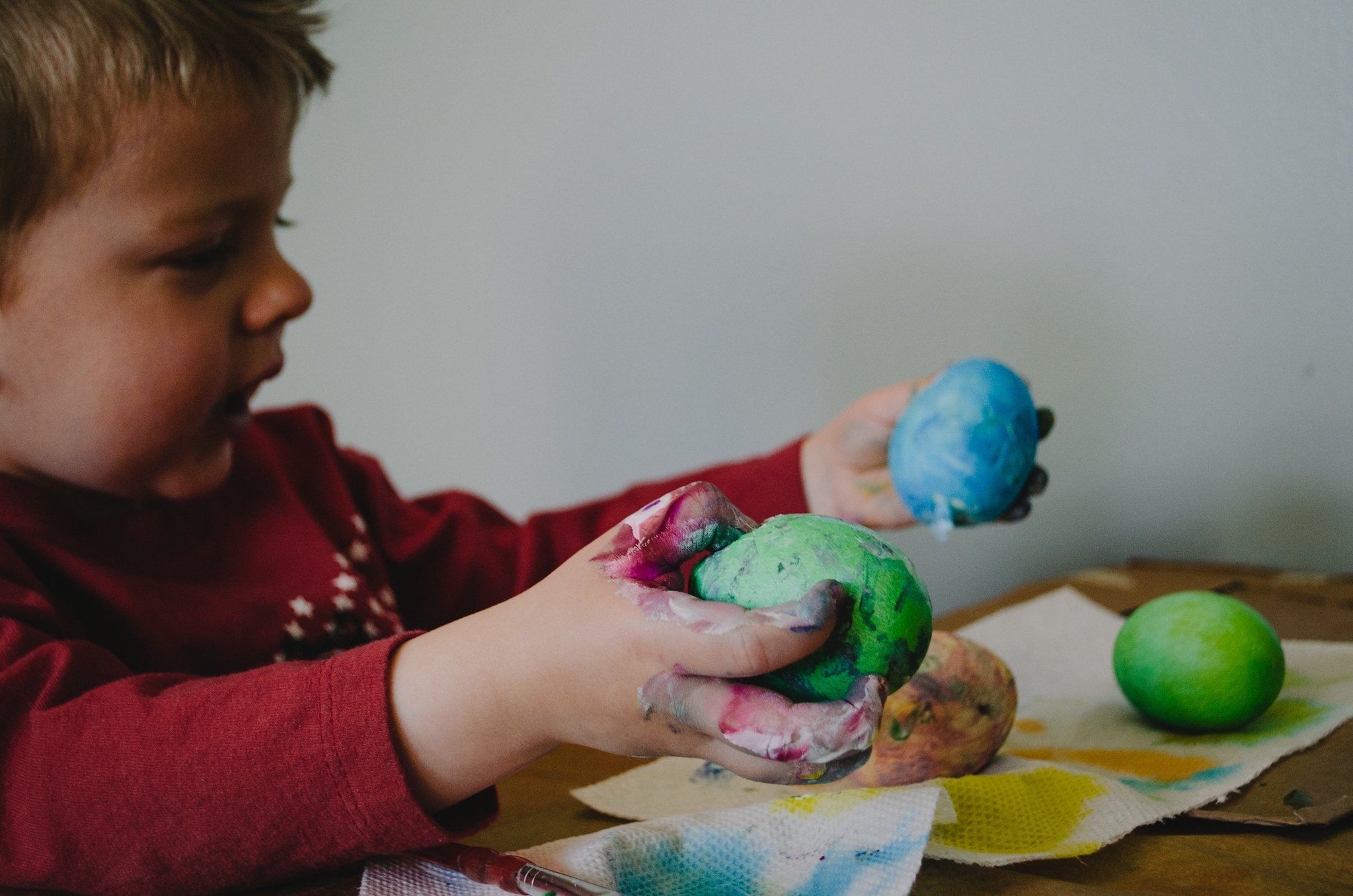boy holding different coloured balls of dough
