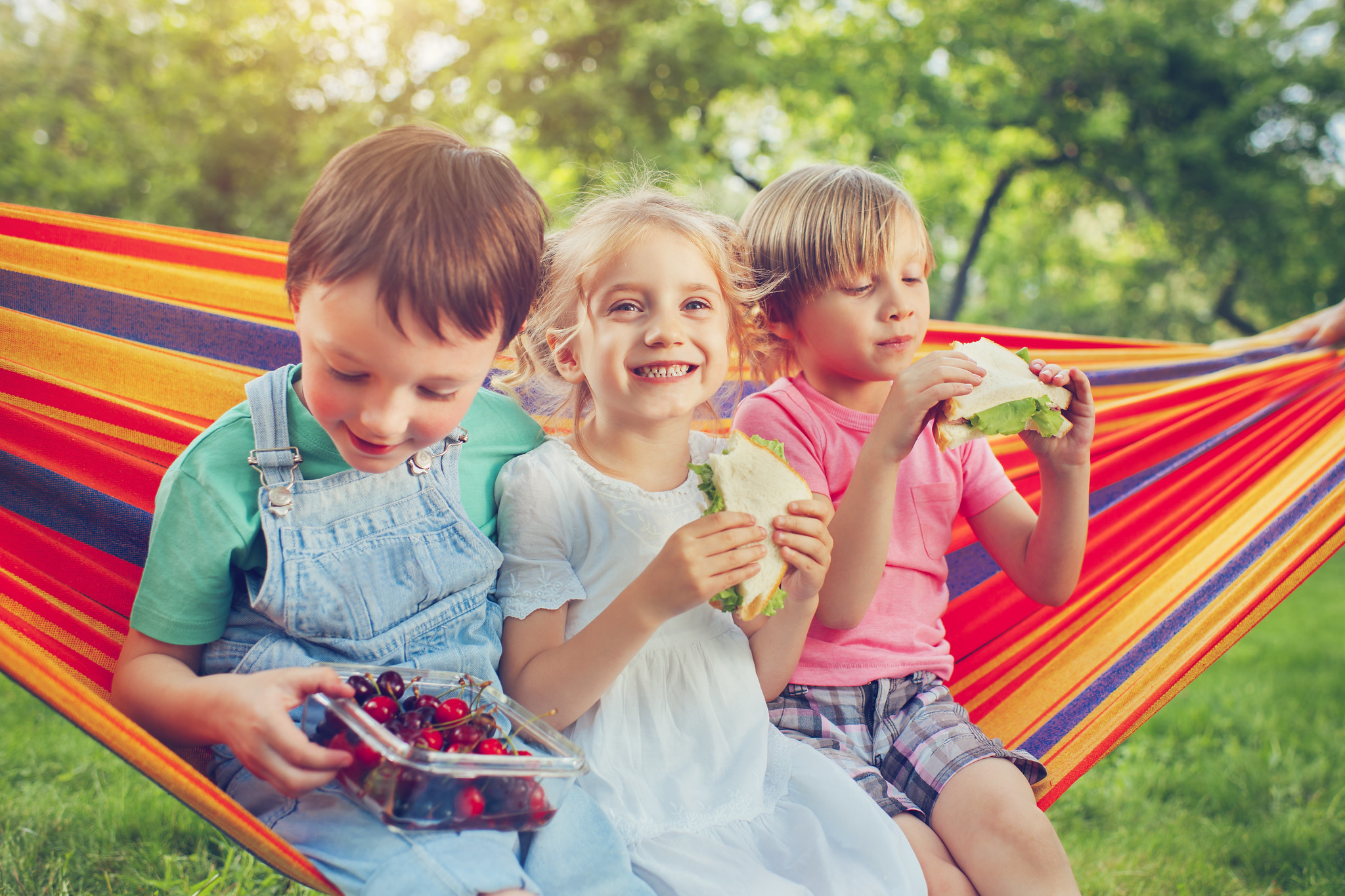 3 children eating sandwiches on a hammock