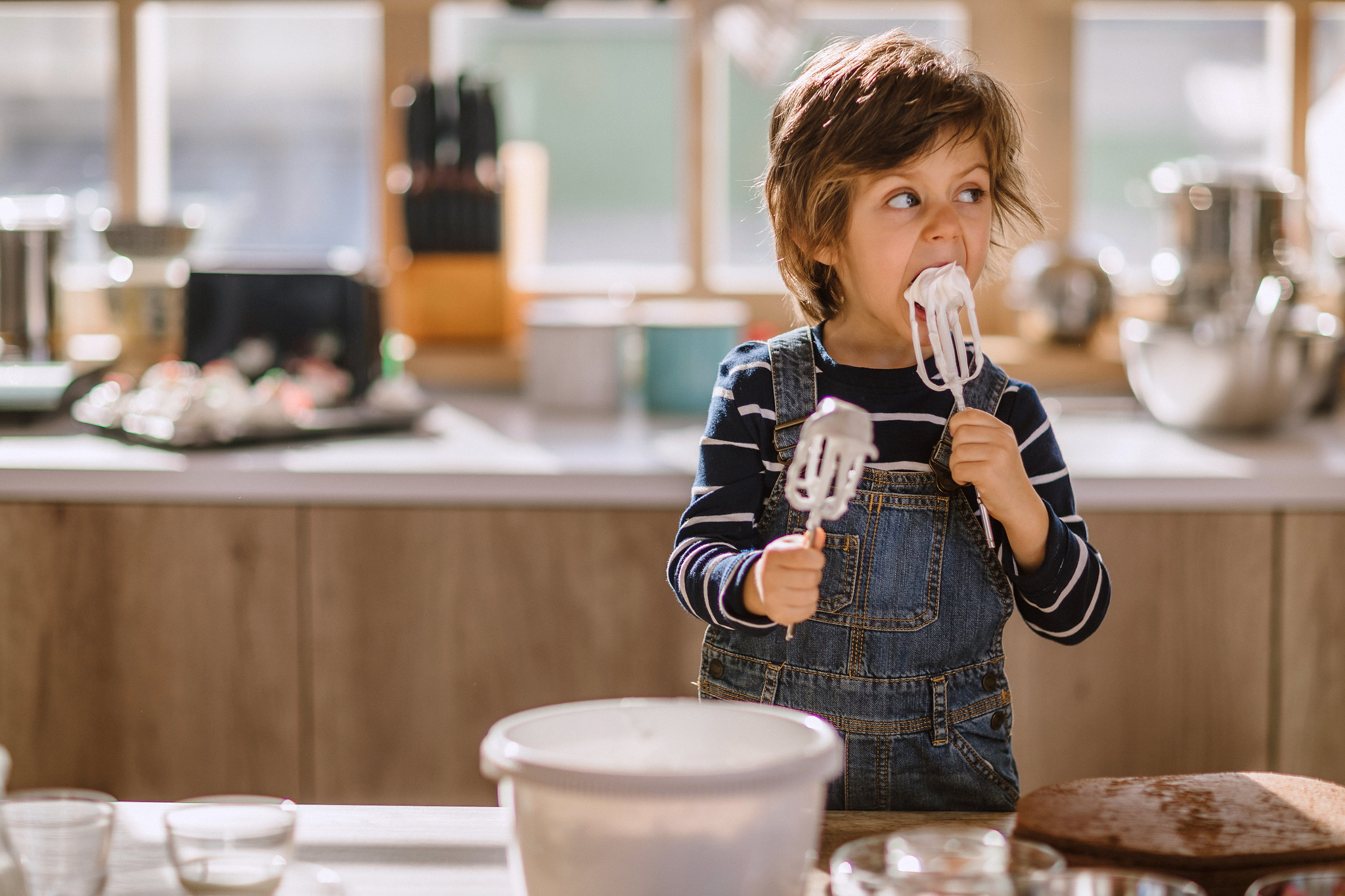 child licking whipped cream off a whisk