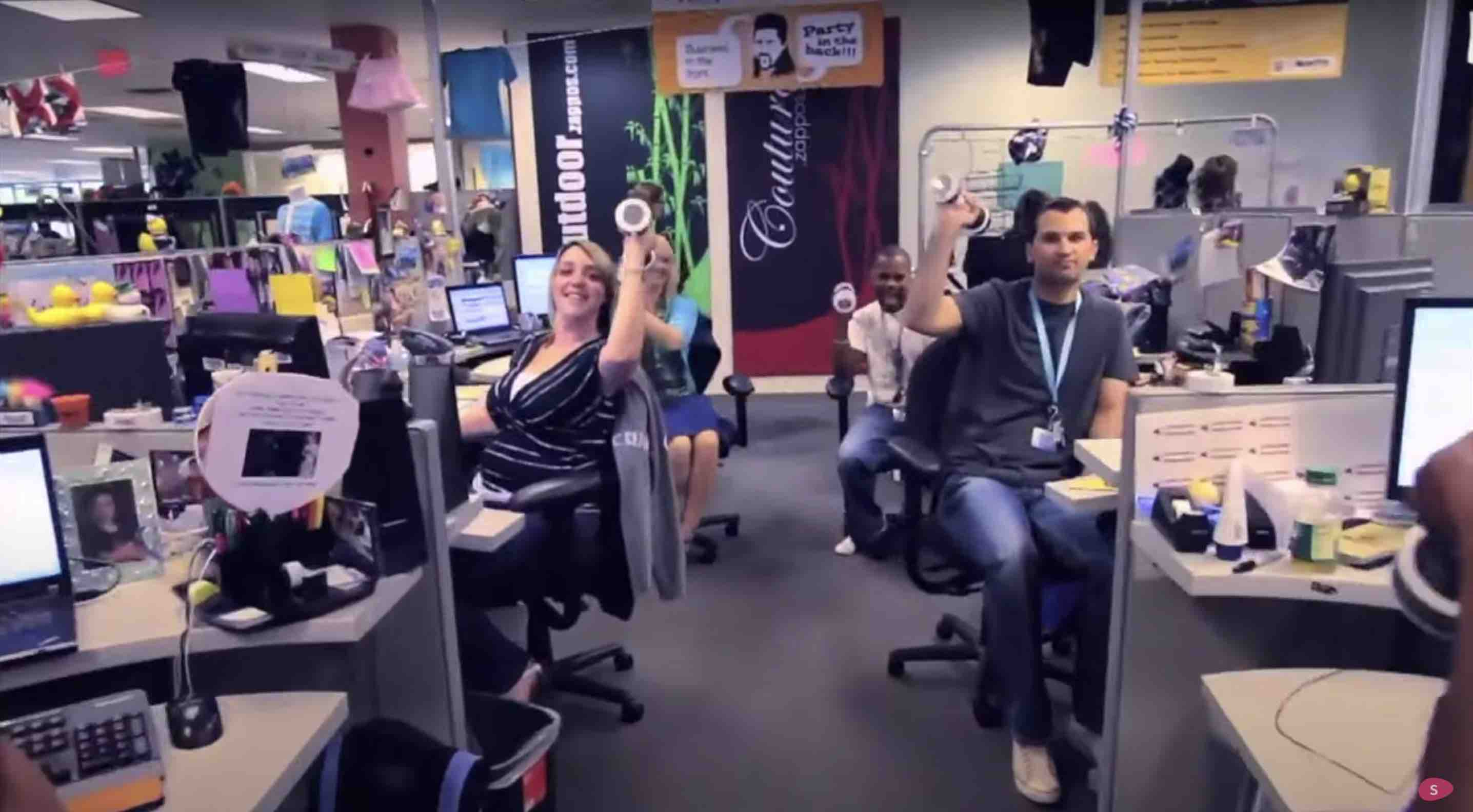 four Zappos employees look at the camera while raising their fists in celebration. A reason why zappos is owned by amazon is culture
