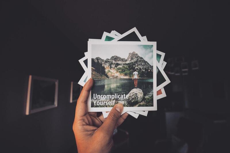 Image contains a hand holding a group of photos