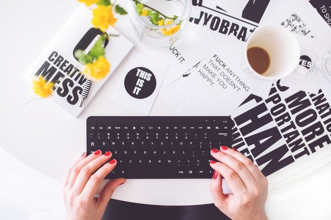 Image contains two hands using a keyboard and a mug over a lot of paper