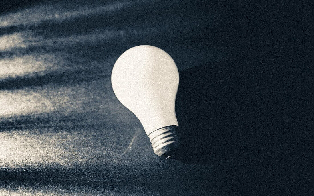 Image contains a light bulb over a black background