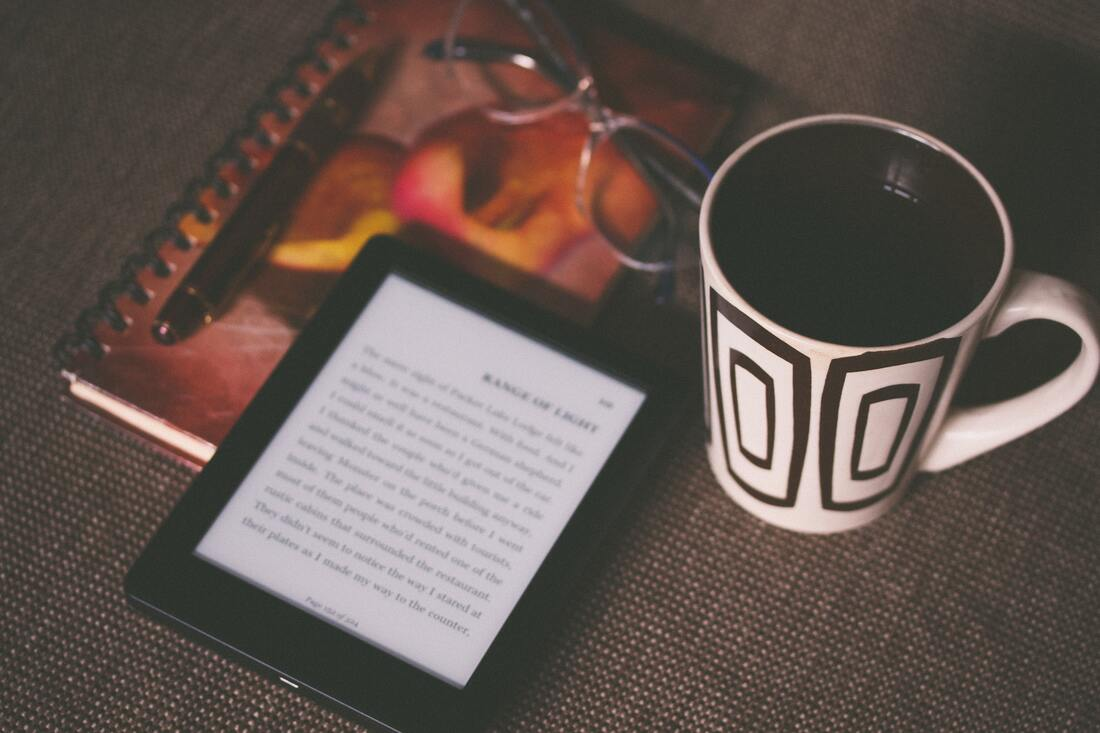 Image contains an ebook and a mug on a top of a table