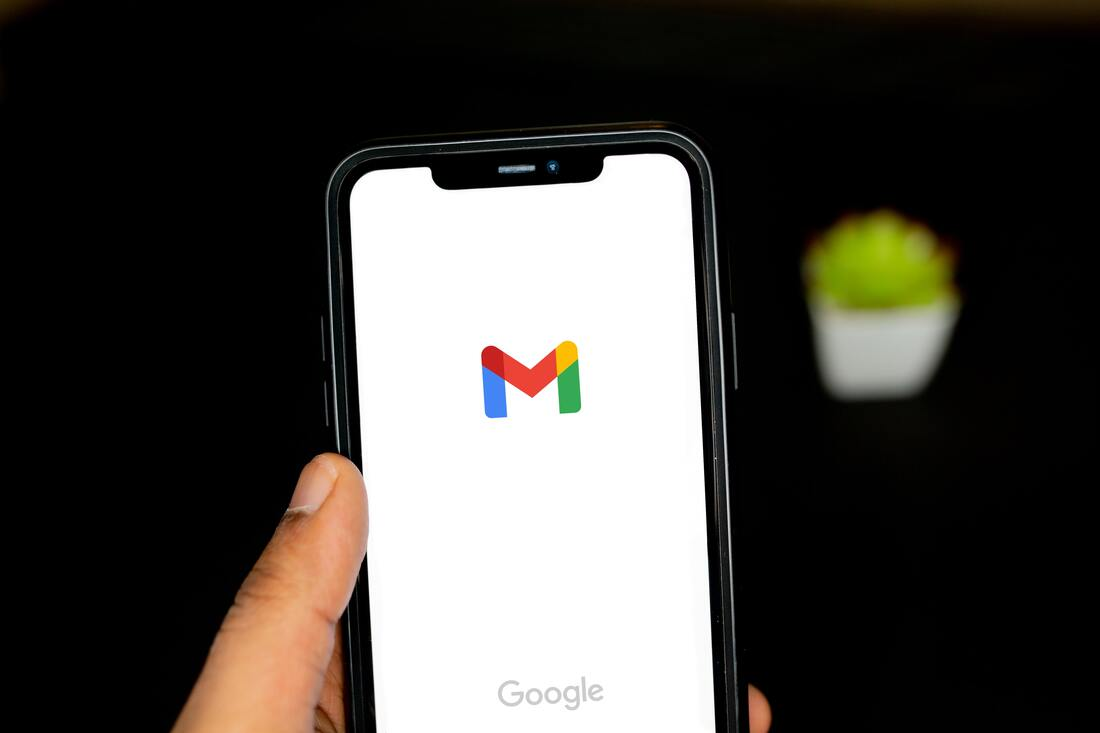 Image contains a cell phone opening the gmail app