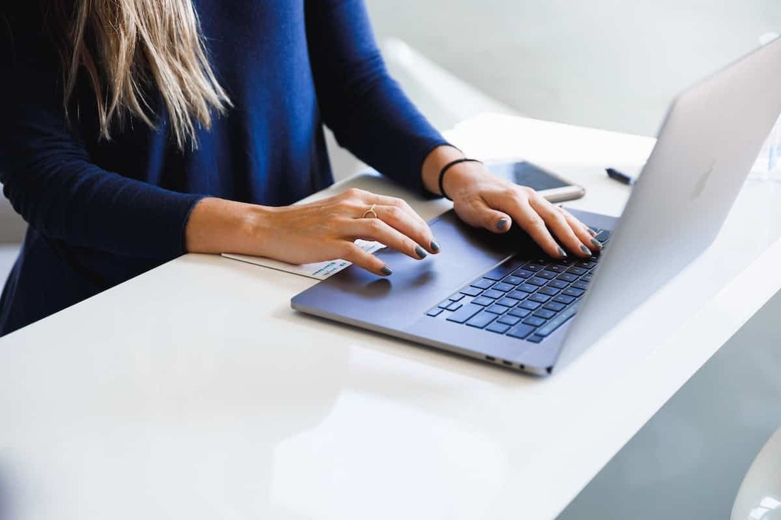 Image contains a woman using a laptop