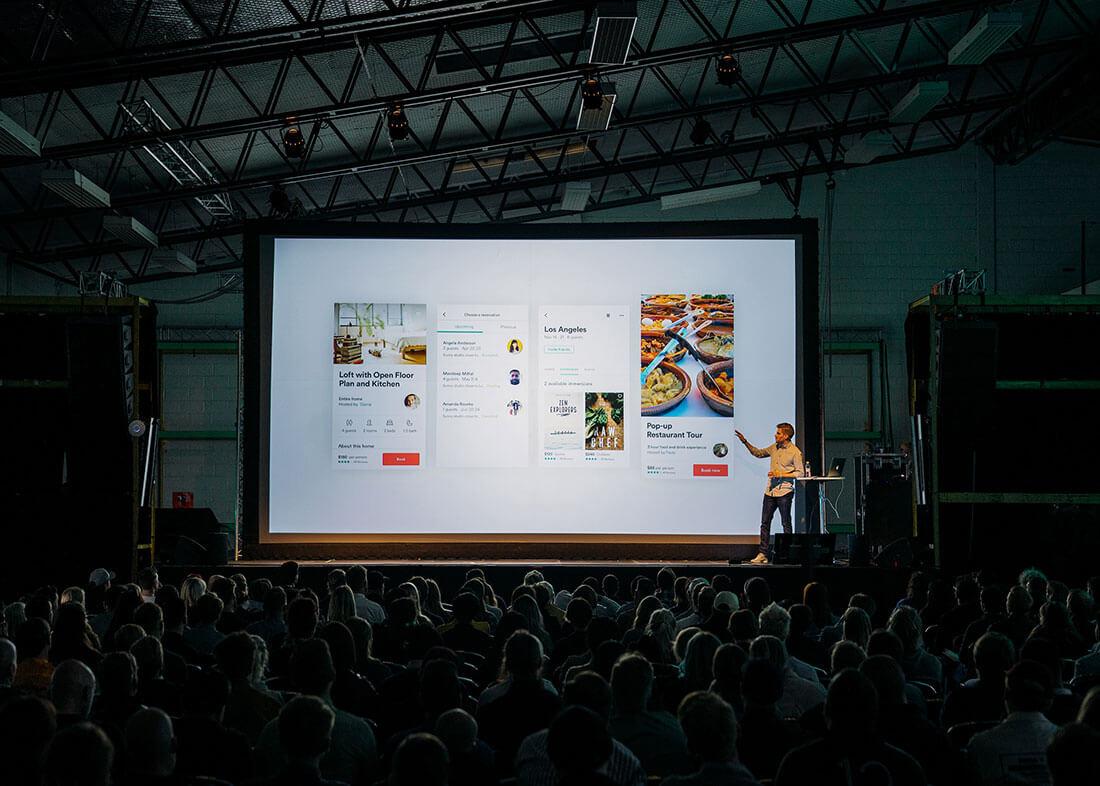 L'image contient une personne présentant et parlant en public devant un auditoire