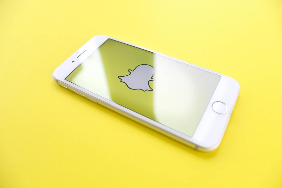 Image contains an iPhone displaying the snapchat logo