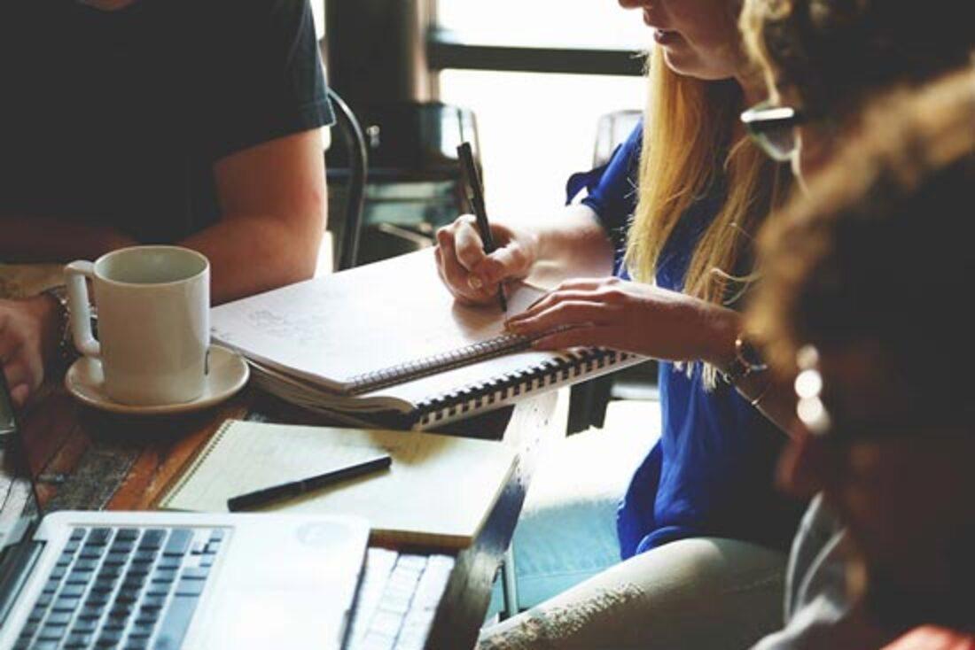 L'image contient des personnes qui écrivent sur un papier et parlent entre elles.