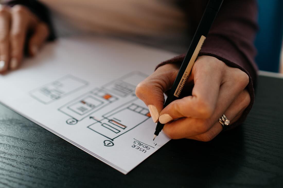 L'image contient une personne qui dessine sur un papier
