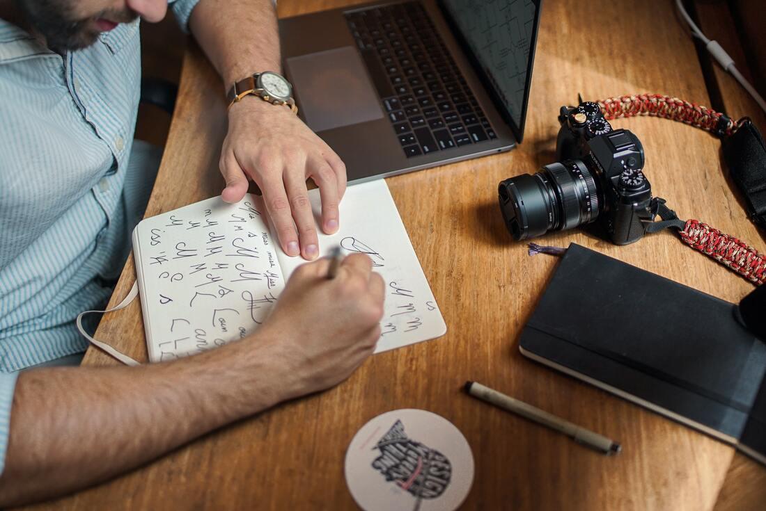 L'image contient une personne écrivant sur un papier à côté de l'ordinateur.