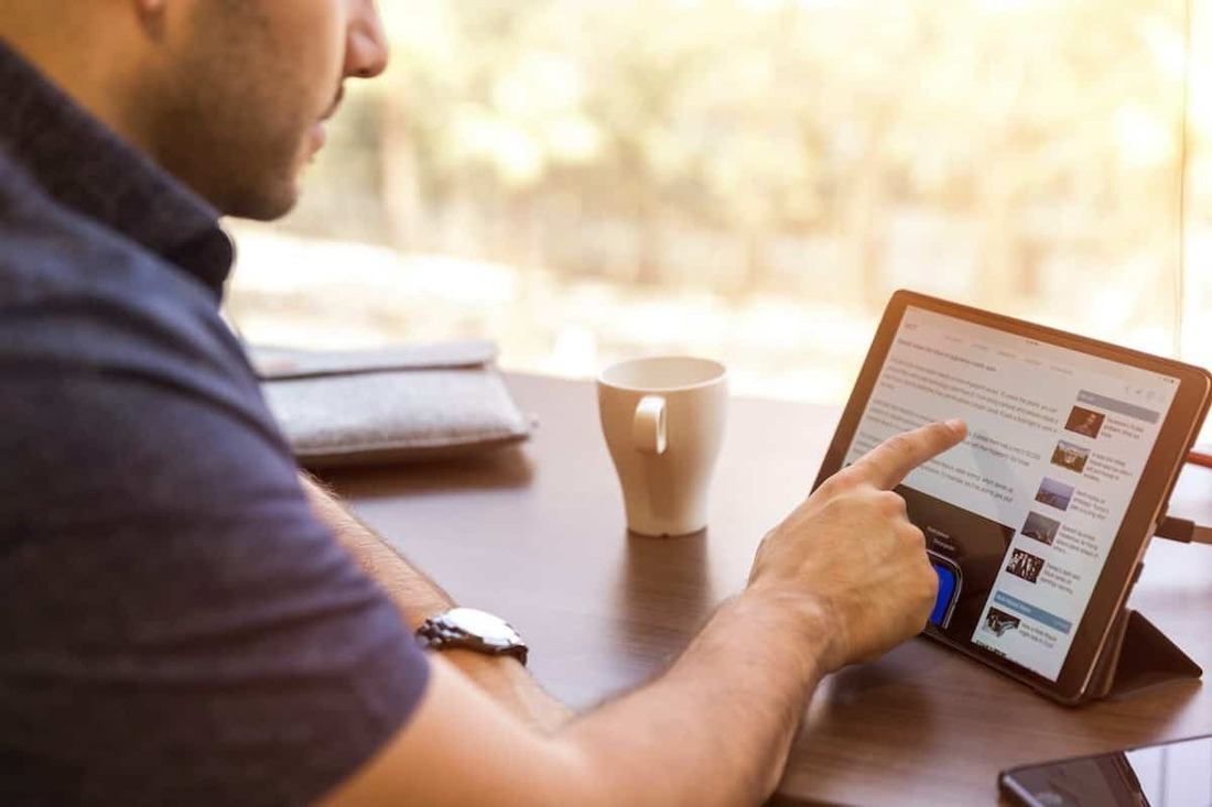 Image contains a person using an iPad
