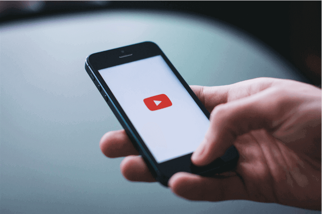 Image contains a phone with YouTube logo on screen