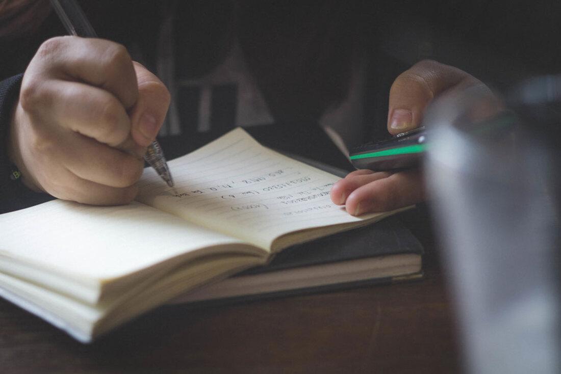 La imagen contiene una persona escribiendo en un papel