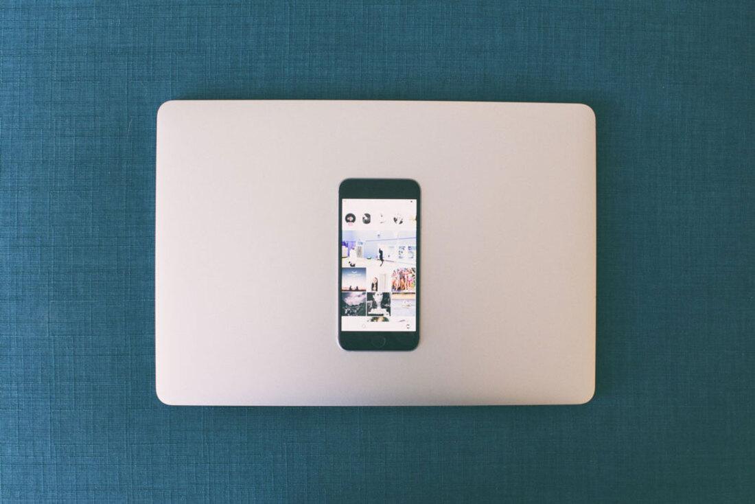 La imagen contiene un teléfono sobre un portátil en la mesa