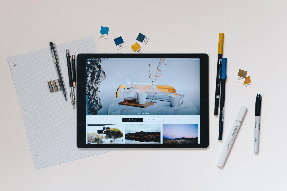 Image contains an iPad displaying photos