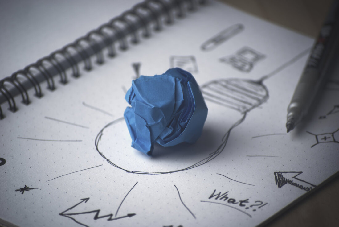 Image contains a ball of paper on a notebook