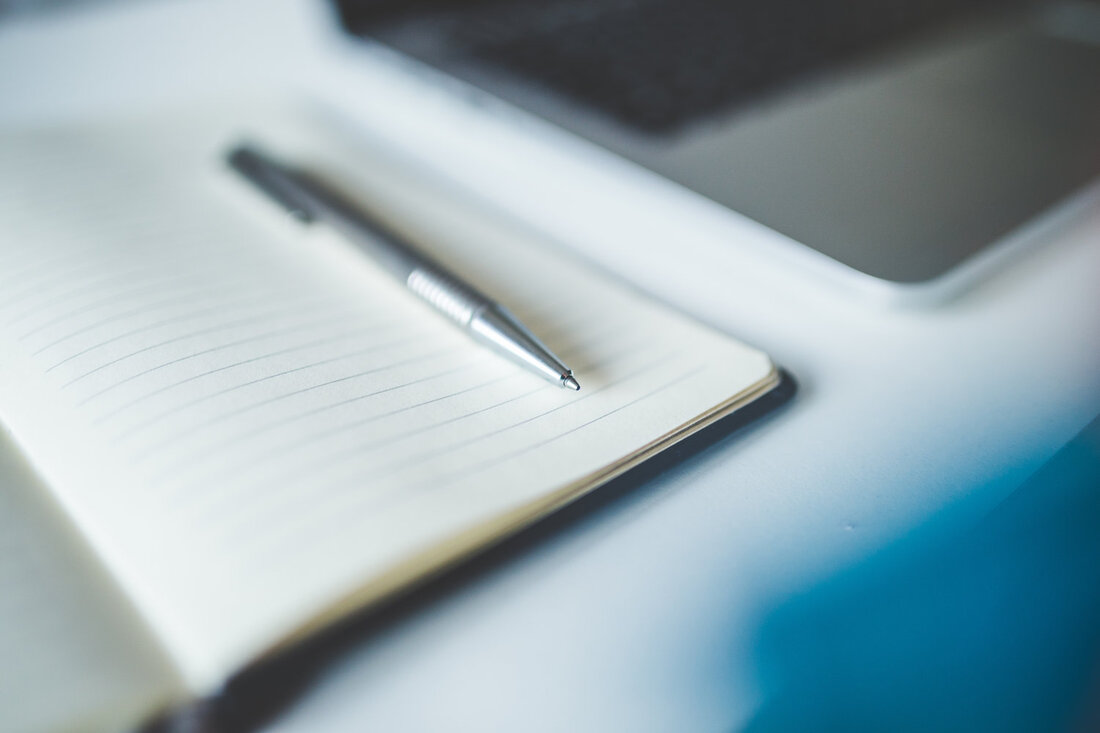 Image contains a pen on a notebook