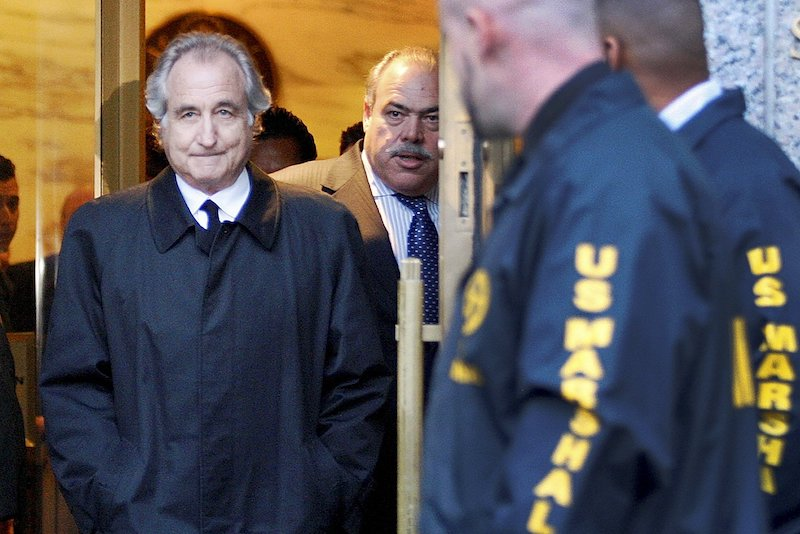 Bernie Madoff scandal concludes with him leaving a courthouse, in front of his lawyer and policemen on his side