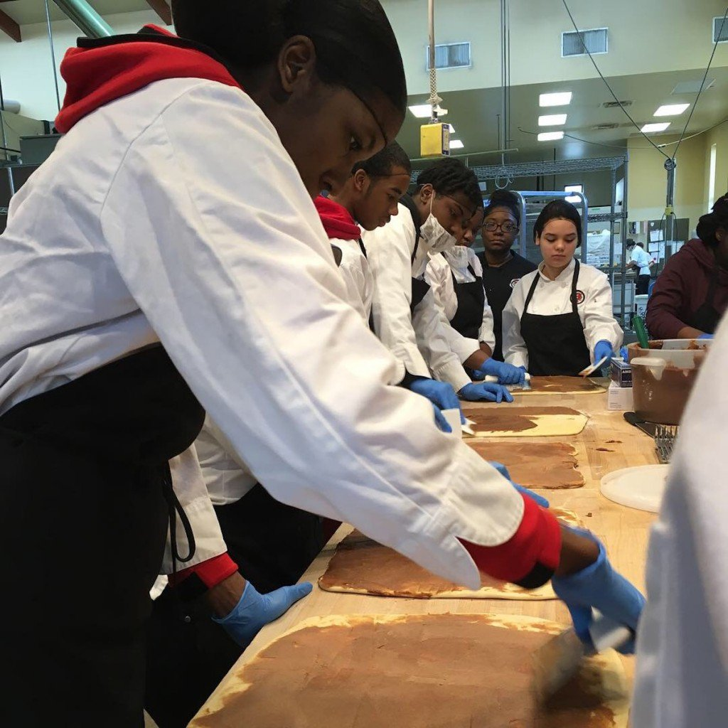 MPS kids work on rolling out cinnamon rolls at Troubadour Bakery in Milwaukee.