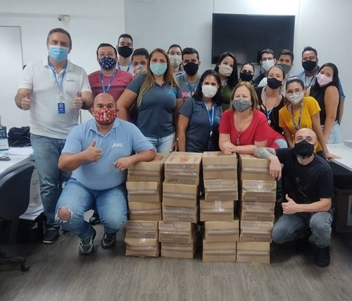 Co-workers with masks posing in front of boxes