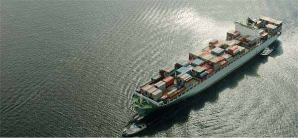 Aerial view of a cargo ship with tug boats.