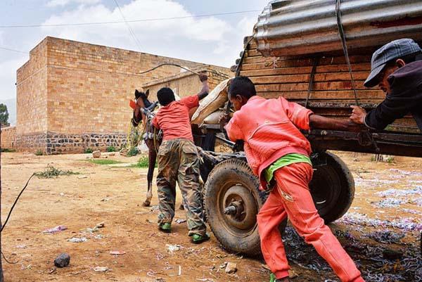 Men assisting a horse drawn cart