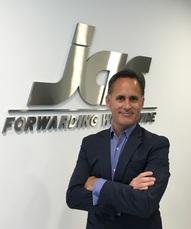 JAS Peru Managing Director, Johnny Delgado, Stands in front of JAS Logo