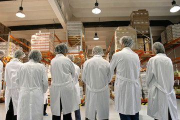 Workers in lab coats and caps in a warehouse.