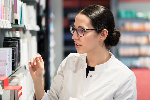 Pharmacist choosing items from a shelf.