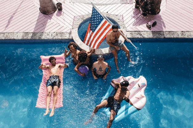 6 employees / juicers in a pool with one of them with an american flag. Two of the guys is floating in the water.