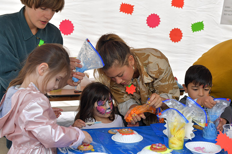 Children with painted faces making cookies