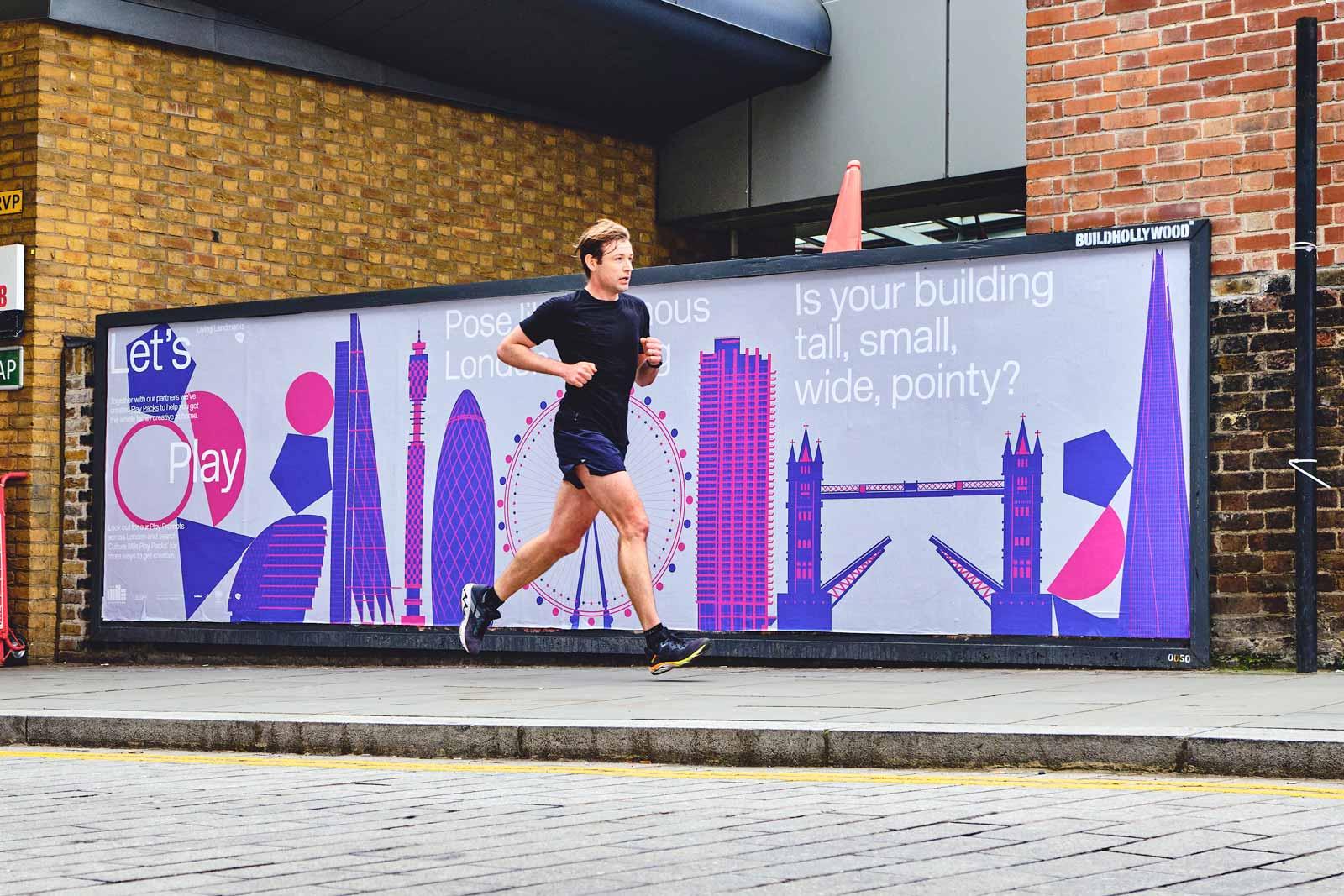 Man running past play packs billboard in the street