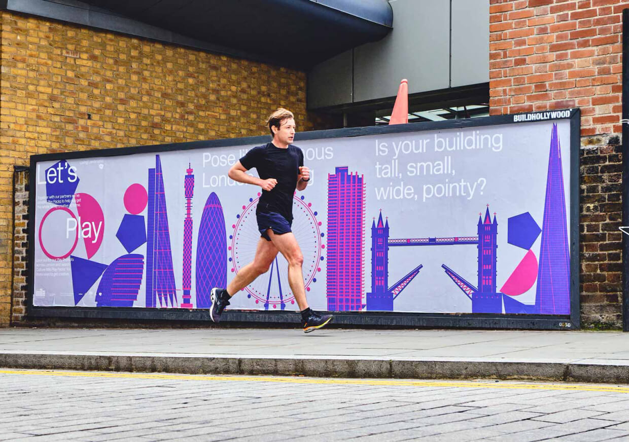 Man running past a play packs billboard on the street.