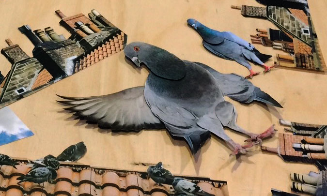 Cut out of pigeons and chimney stacks on table