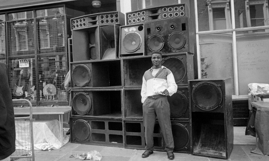 A man standing in front of a bank of loud speakers
