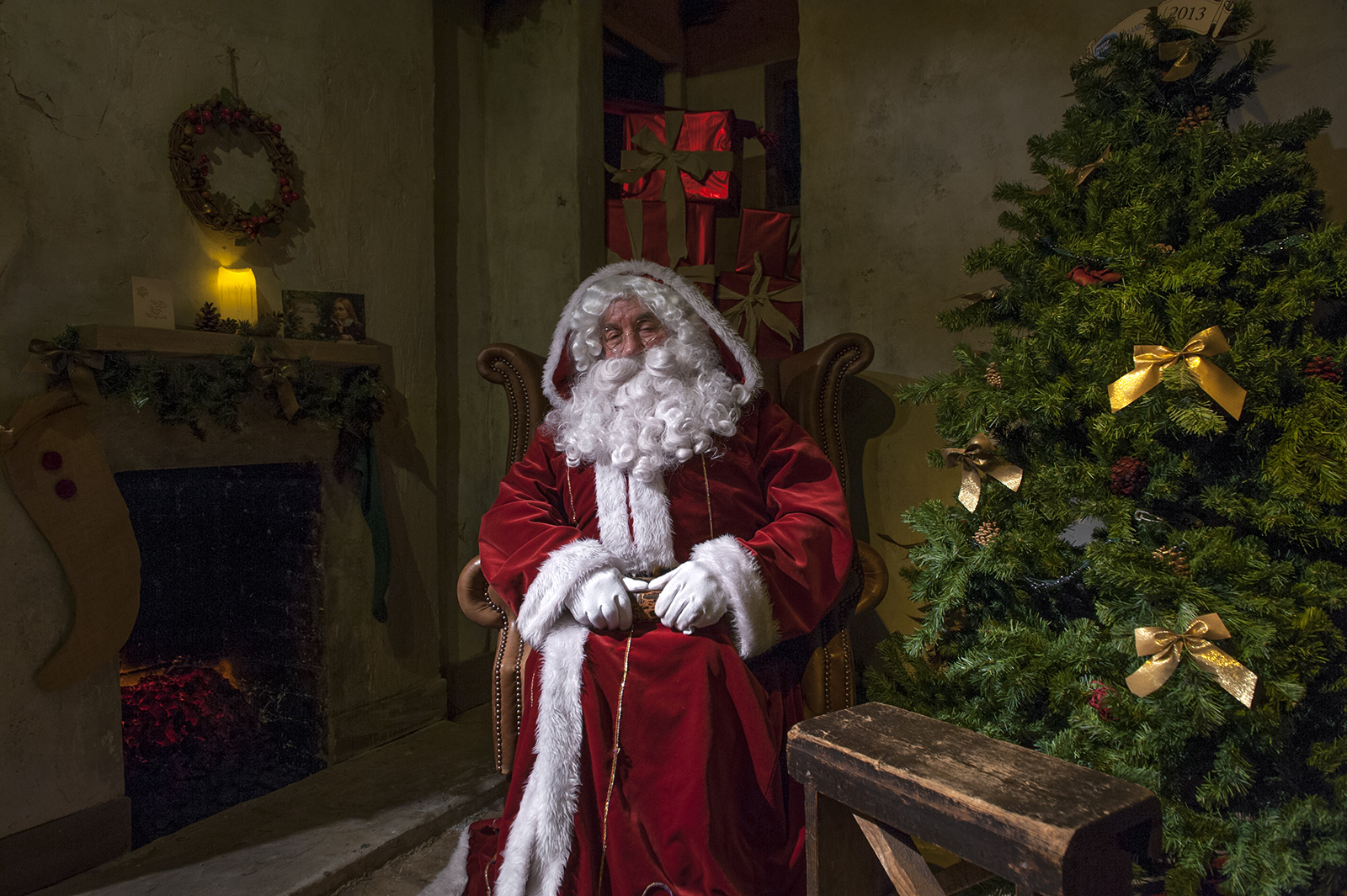 Santa sitting on a chair next to a Christmas tree and fireplace