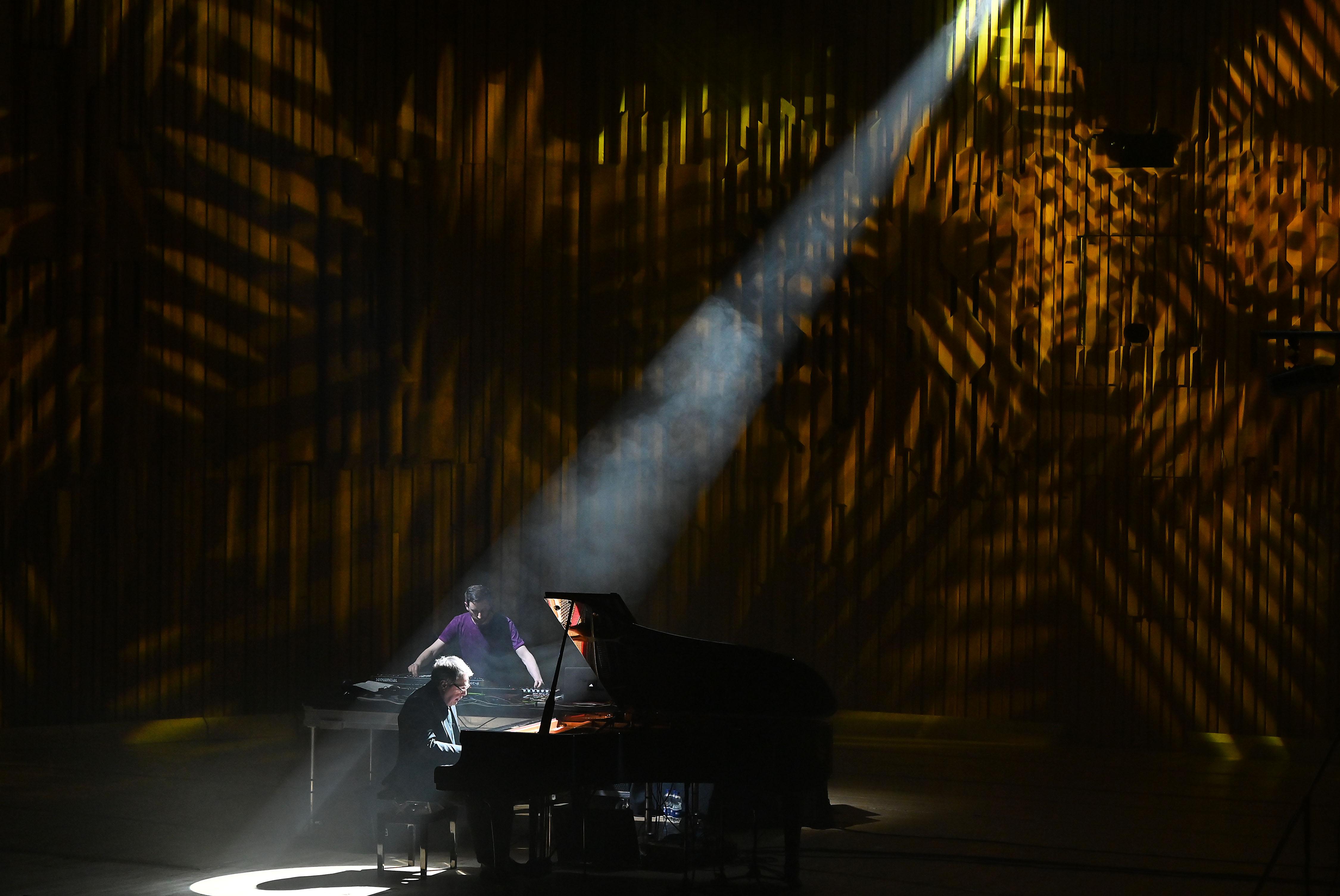 Pianist performing under a spotlight