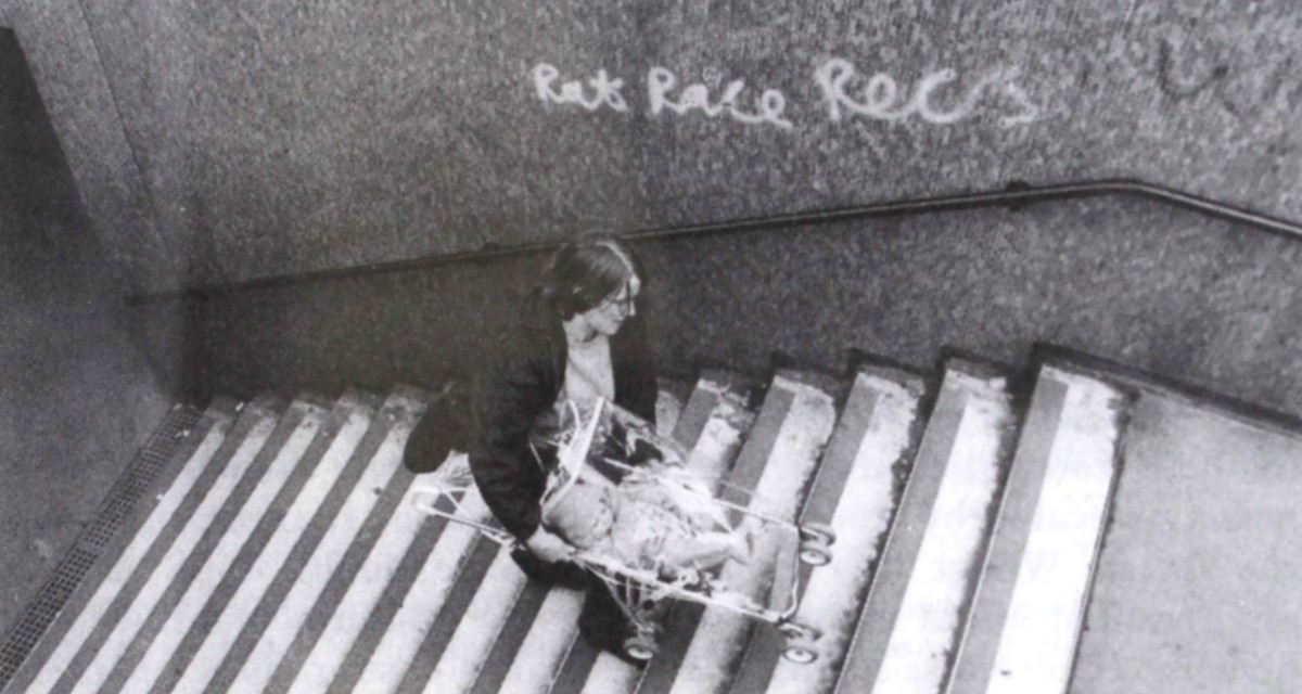 Black & White image of woman carrying a pram up a set of stairs