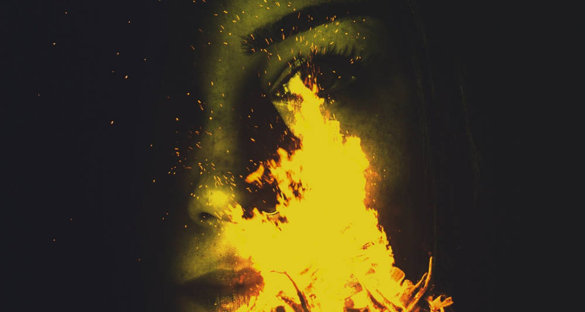 A close up image of a woman's face obscured by a campfire