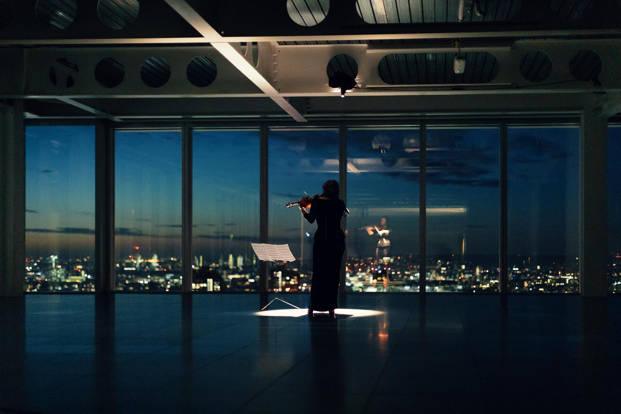 Woman playing violin in empty room at night with city skyline showing through window