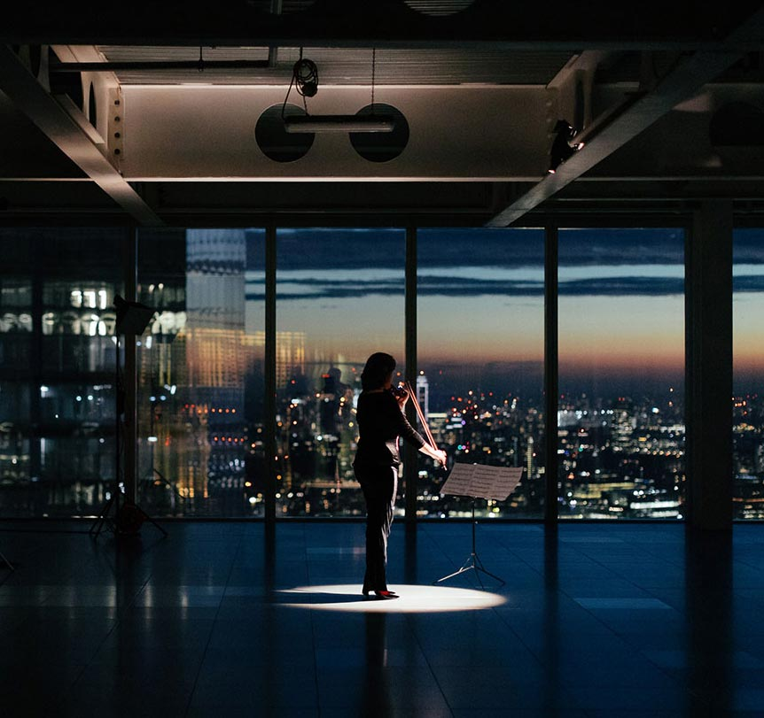 Woman playing instrument in empty room with London skyline backdrop out of window
